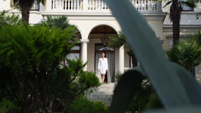 stockvideo's en b-roll-footage met woman enjoying the morning - formal garden