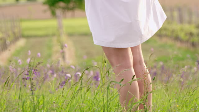SLO MO femme profitant de la brise de l'été dans l'herbe