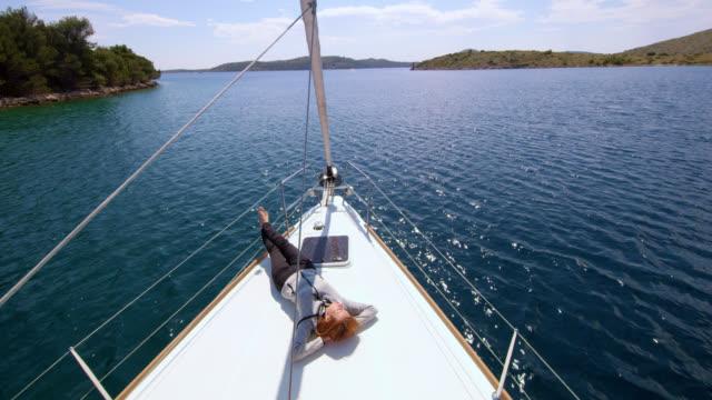 vídeos de stock e filmes b-roll de ws woman enjoying the sun and the wind on a sailboat - convés