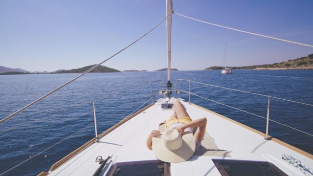Mujer DS disfrutando del sol en una cubierta de un velero