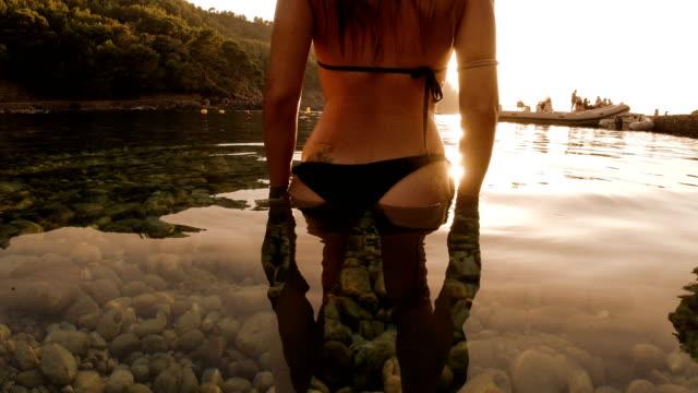vídeos de stock e filmes b-roll de woman enjoying the sunset at a lonely beach - biquíni