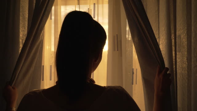 woman enjoying the sunset by the window. - waking up stock videos & royalty-free footage