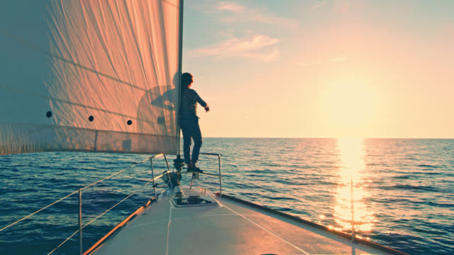 ws woman enjoying the sunset from a sailboat's bow - ship's bow stock videos & royalty-free footage