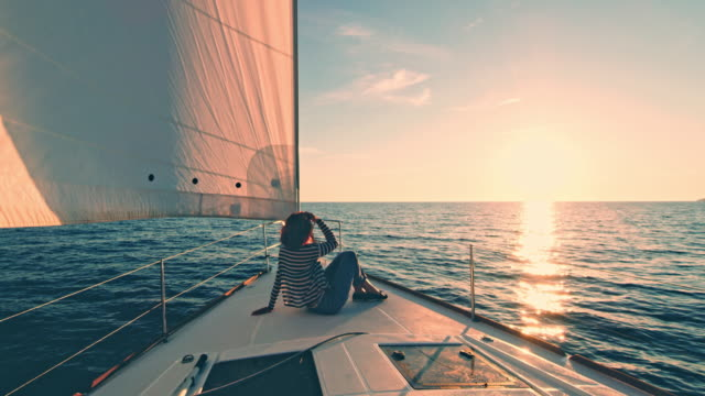 vídeos de stock e filmes b-roll de ds woman enjoying the sunset on a deck of a sailboat - barco