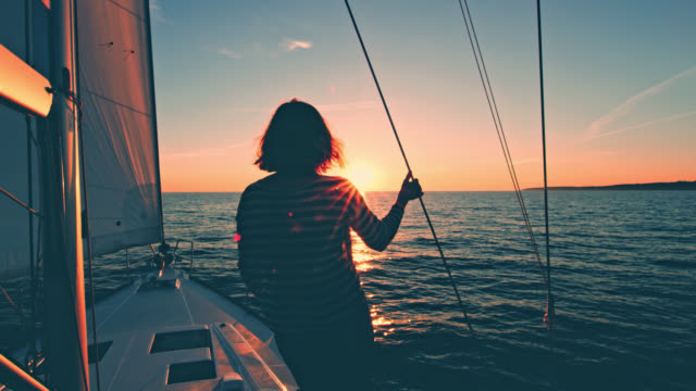 ws woman enjoying the sunset on a deck of a sailboat - rear view stock videos & royalty-free footage