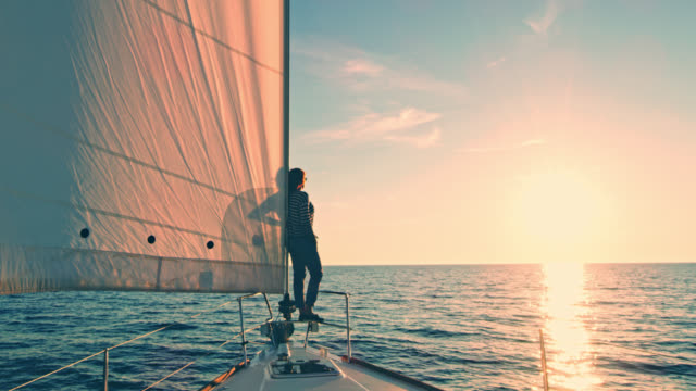 ws td woman enjoying the sunset on a sailing sailboat - ponte di una nave video stock e b–roll