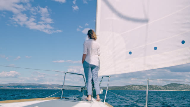 WS Woman enjoying the view from a deck of a sailing sailboat