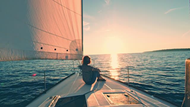 vídeos y material grabado en eventos de stock de ws mujer disfrutando de la vista de una puesta de sol en un barco - verano