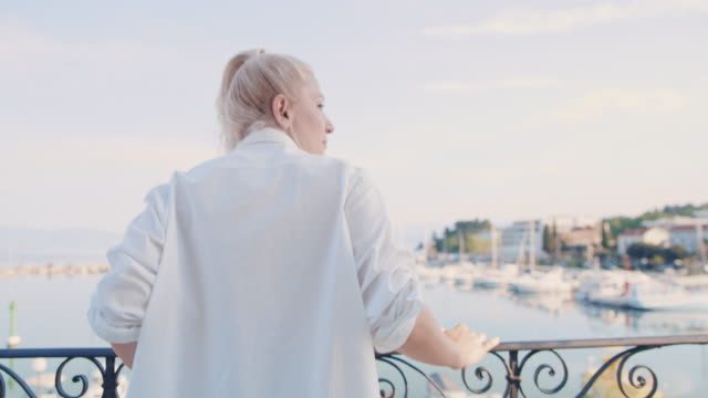 ws woman enjoying the view on the balcony by the sea - white shirt stock videos & royalty-free footage