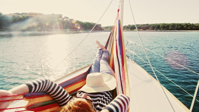 ws woman enjoying the wind and fresh air on a sailboat - hammock stock videos and b-roll footage