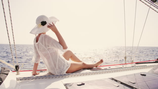 slo mo woman enjoying the wind on a sailboat - sun hat stock videos & royalty-free footage