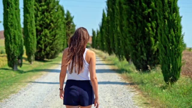 woman enjoying tuscany in a cypress alley - vista posteriore video stock e b–roll