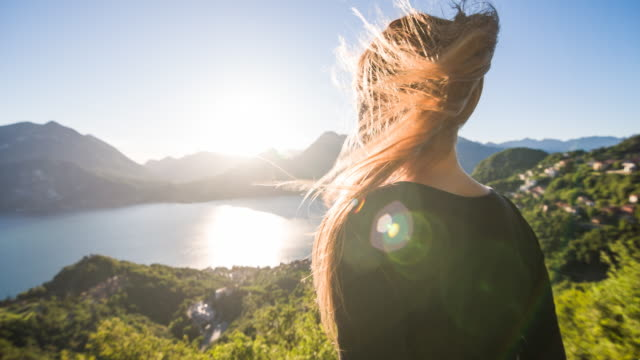 woman enjoying view of lake on a windy day - mountain range stock videos & royalty-free footage