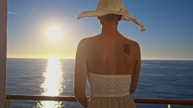 slo mo woman enjoying view over the sea at sunset - sun hat stock videos & royalty-free footage