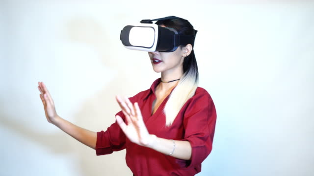 woman enjoying watching 3D simulation video from virtual reality (VR) headset - people and technology concept