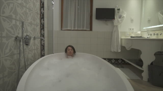 a woman enjoys a bubble bath in a bathtub at a luxury resort. - bubble bath stock videos and b-roll footage