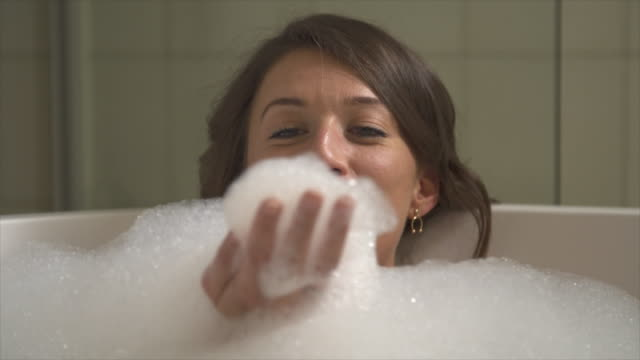 a woman enjoys a bubble bath in a bathtub at a luxury resort. - vasca da bagno video stock e b–roll