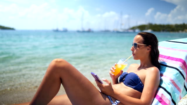 woman enjoys a sunny day relaxing by the sea - one young woman only stock videos & royalty-free footage