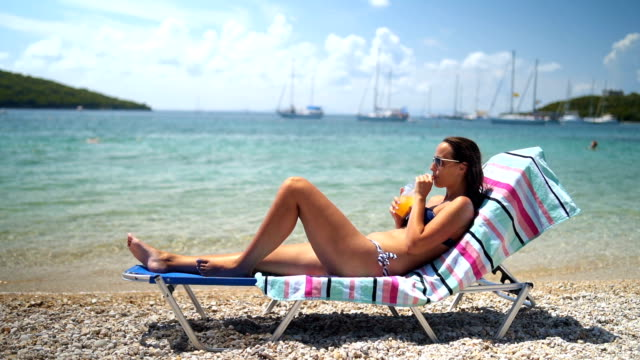 woman enjoys a sunny day relaxing by the sea - lounge chair stock videos & royalty-free footage