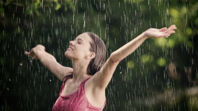 Woman enjoys and stretches her arms in summer rain