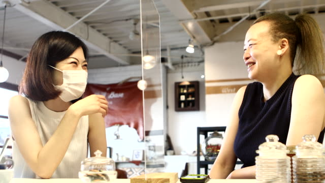 a woman enjoys chatting at a cafe that has reopened for business - 動画関連点の映像素材/bロール