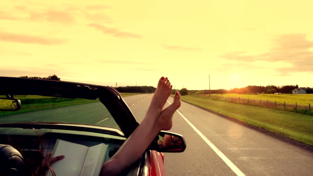 Woman enjoys freedom on the highway in car