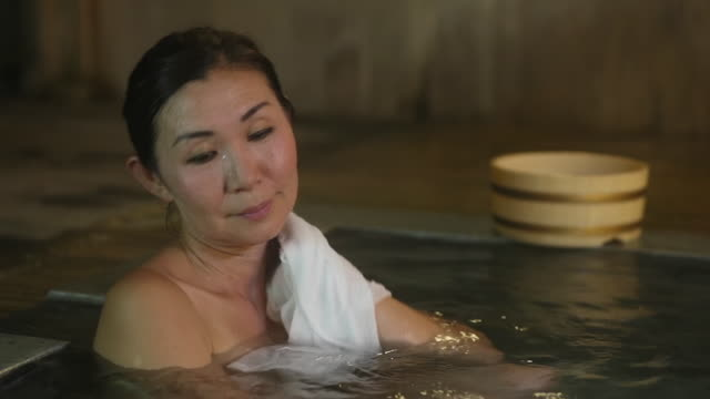 woman enjoys japanese style hot bath - oita prefecture stock videos & royalty-free footage
