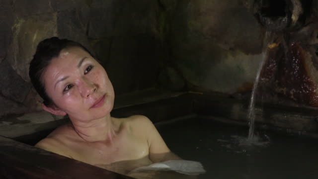 woman enjoys ofuro, hot spring, at an onsen hot spring resort in mt. aso area, kumamoto, japan - taking a bath stock videos and b-roll footage