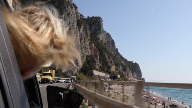 Frau genießt Pkw-Fahrt entlang der Küstenstraße