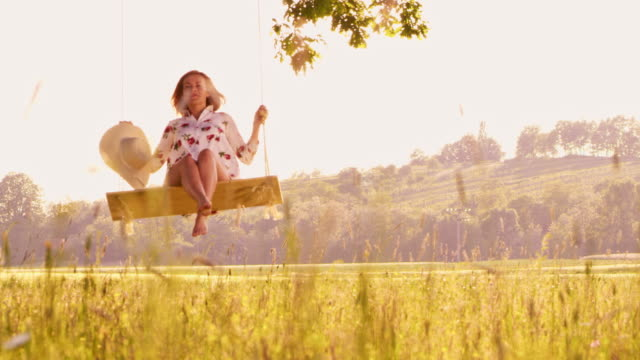 slo mo ds woman enjoys swinging in the countryside - back lit stock videos & royalty-free footage