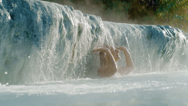 super slo mo woman enjoys thermal water cascading at the saturnia hot springs - hot tub stock videos & royalty-free footage