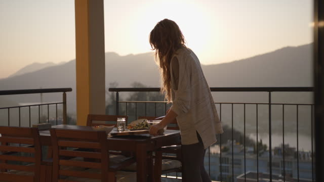 woman enjoys view of sunset while preparing dinner - standing stock videos & royalty-free footage