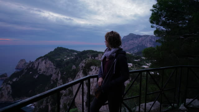 woman enjoys view of the cliffside coast of capri in italy on cloudy day - mid length hair stock videos & royalty-free footage