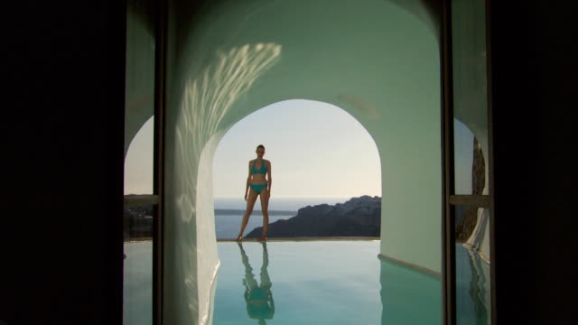 A woman entering a luxurious pool