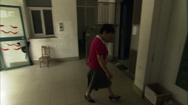 vídeos de stock, filmes e b-roll de ws pan woman entering apartment building lobby and taking discarded milk containers out of recycling box, shanghai, china - só uma mulher madura