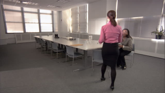 Woman entering conference room / shaking hands with woman getting up from conference table / women sitting down and opening binders / talking
