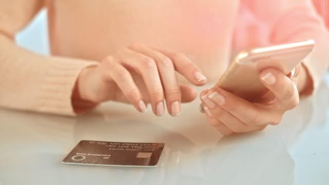 vídeos de stock, filmes e b-roll de slo mo mulher inserir informações de cartão de crédito para o telefone - gastando dinheiro