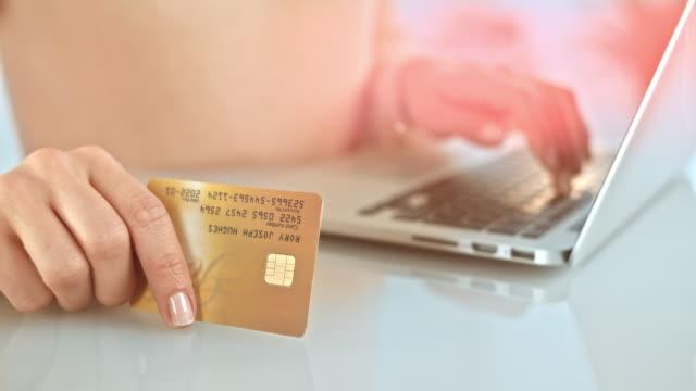 vídeos de stock, filmes e b-roll de slo mo mulher digitando suas informações de cartão de crédito para laptop - gastando dinheiro
