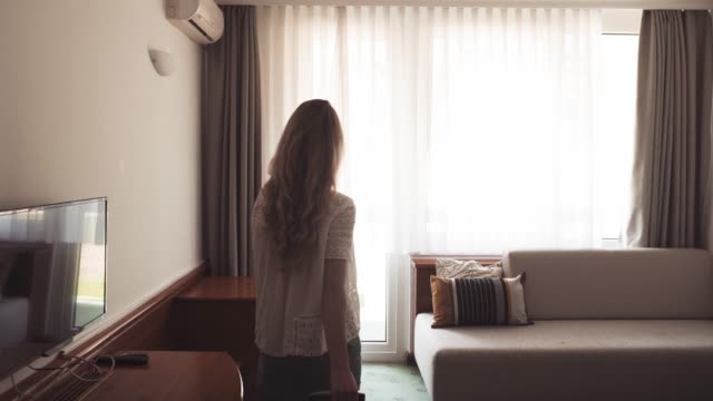 woman entering hotel room and checking the view - domestic room stock videos & royalty-free footage
