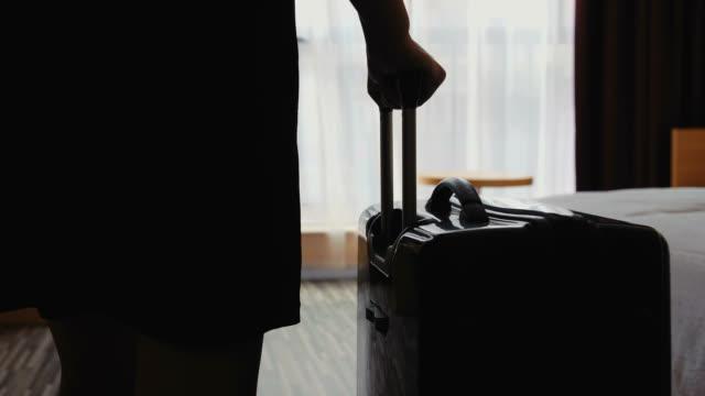 vidéos et rushes de femme entrant dans la chambre d'hôtel avec bagages - une seule femme d'âge moyen