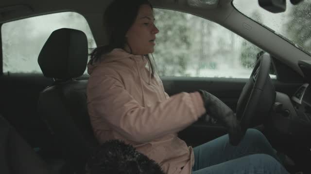 vidéos et rushes de femme entrant dans la voiture après avoir nettoyé le pare-brise de la neige - glacé