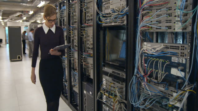 MS Woman entering, inserting cables in server and leaving, Sydney, Australia