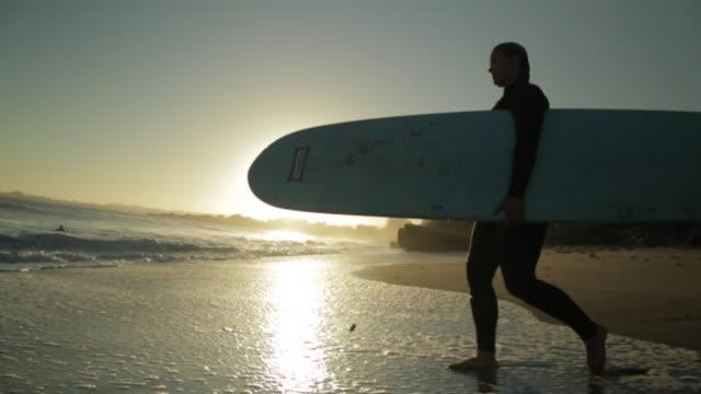slo mo woman entering ocean w/ surfboard - カリフォルニア州サンタクルーズ点の映像素材/bロール
