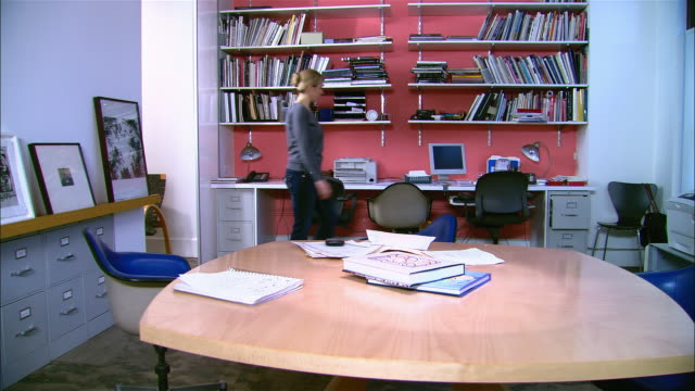 vídeos de stock e filmes b-roll de woman entering office and sitting down to work on documents at conference table - sentar se