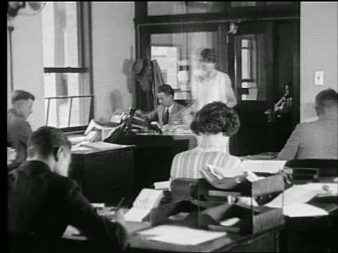 B/W 1927 woman entering office where men + women work at desks / industrial