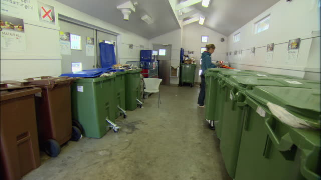 ws pan woman entering recycling room and sorting waste into various containers / malmo, sweden - malmo stock videos and b-roll footage