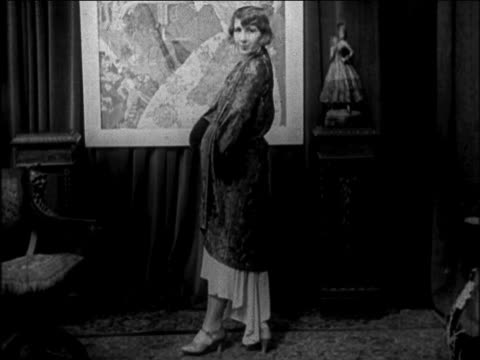 B/W 1922 woman entering room modeling coat / she removes it to reveal dress / newsreel