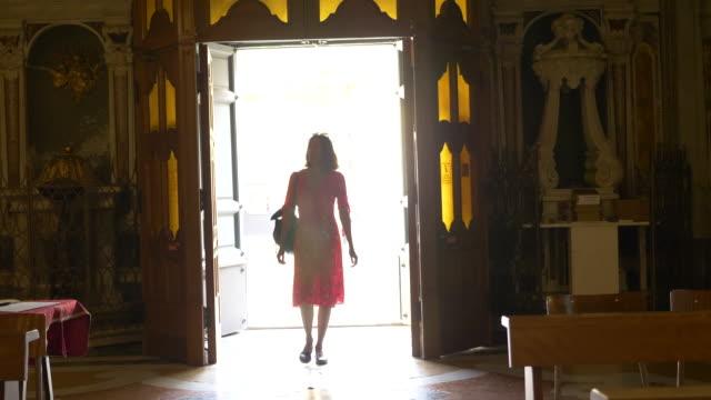 vídeos y material grabado en eventos de stock de a woman enters a church in a luxury resort town in italy, europe. - slow motion - entrando