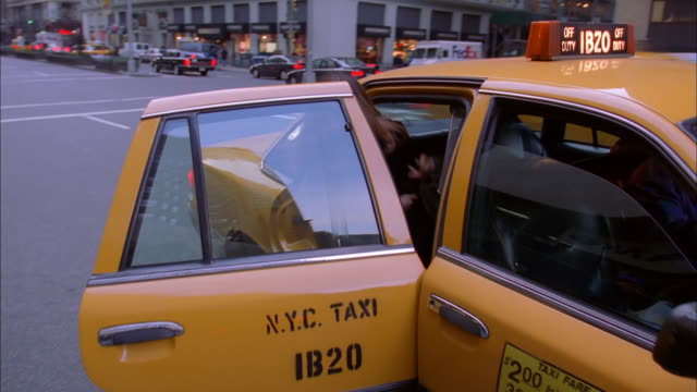 a woman enters a taxi in new york city, then drives away. available in hd. - 乗る点の映像素材/bロール
