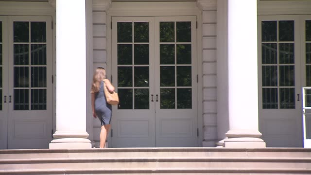 a woman enters city hall doors - lawyer stock videos and b-roll footage